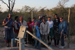 Taylor and other volunteers standing around newly constructed well smiling