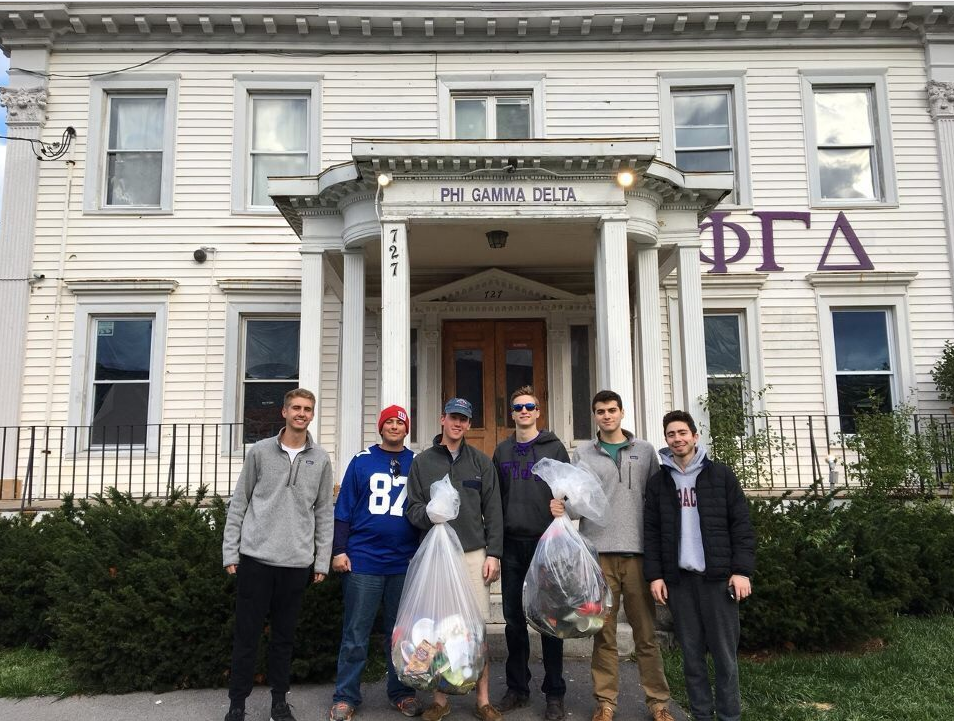 6 men in front of fraternity house with bags of trash