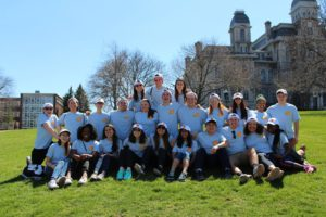 group of volunteers wearing The Big Event shirts sitting on the quad