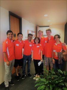 7 students in orange shirts