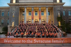 "Marching band assembled on steps of Carnegie library with sign reading ""Welcome to the Syracuse Family"""