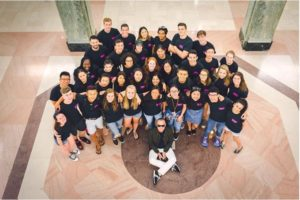 Group of 30 students wearing matching tshirts looking up at camera
