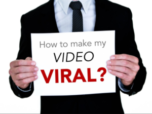 "man in a suit holding a sign that says ""how to make my video viral"""