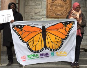 "Two individuals are holding a large white sheet with a monarch butterfly painted on it and the words, ""No human being is illegal"""