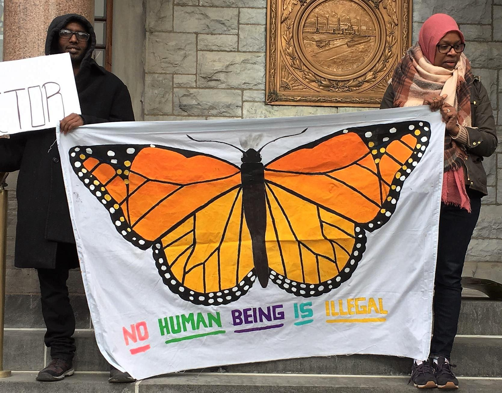 """Two individuals are holding a large white sheet with a monarch butterfly painted on it and the words, """"No human being is illegal"""""""