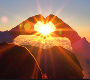 person standing before mountains at sunset just as sun approaches horizon line, she is holding her hands up in the shape of a heart so that the sun rays pass through the heart made of her hands
