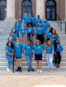 BBB staff wearing matching bright blue tshirts posing on steps in front of Carnegie Hall