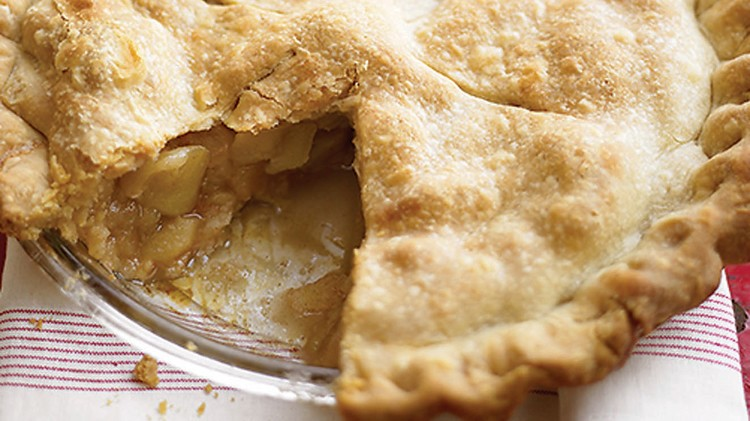 fresh apple pie with large piece cut out; crust is golden brown with fluted edge