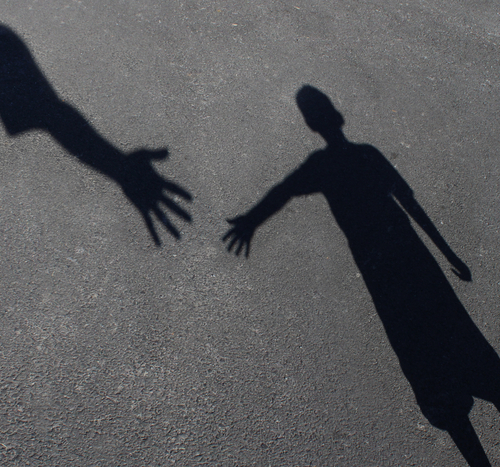 two shadow figures on pavement extend hands toward each other