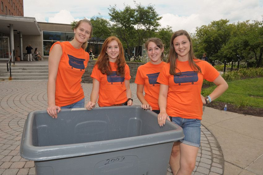4 college women dressed in orange Goon Squad tshirts standing around a large plastic bin in the Sadler courtyard area