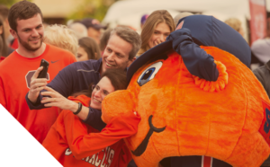 family dressed in orange SU wear taking a selfie with Otto