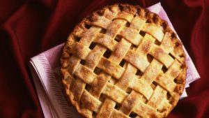 overhead shot of a fresh baked apple pie with a lattice crust on a maroon table cloth