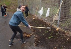 young woman raking soil