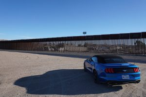 Car w/ texas license plates parked in front of us mexico border wall