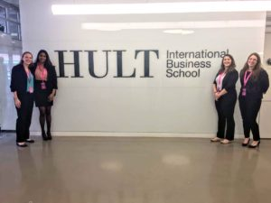 Patty Terhune, Anjali Alwis, and teammates in front of Hult Business School sign