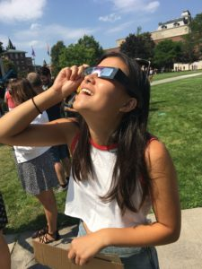 Grace Crummett smiling up at eclipse with cardboard glasses