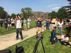 crowd on quad using glasses to look at eclipse