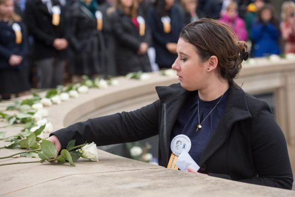 Picture of a past Remembrance scholar laying a rose on the Remembrance wall