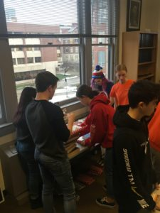 Students gathered around a table wrapping books