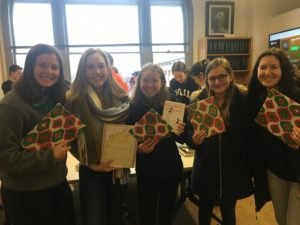 Students smiling and holding holiday wrapped books