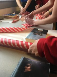 Close up of hands wrapping a book with holiday paper