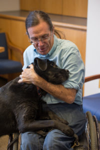 Prof. Bill Peace hugging the head of his black lab support dog, Kate. Bill is seated in his chair, wearing a blue shirt, hair pulled back in pony tail, he is smiling.