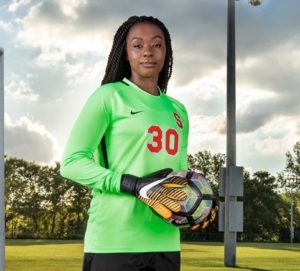 Picture of Santita in soccer uniform, carrying a soccer ball