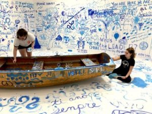 """Art in Life Students painting the """"Refugee Boat"""""""